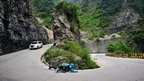 French roller man Jean-Yves Blondeau slides around a corner of the road down the  Tianmen Mountain in Zhangjiajie in China's Hunan province.