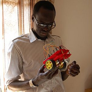 Solomon King, the founder of Fundi Bots, holds one of the kit robots they use at their robotics camps
