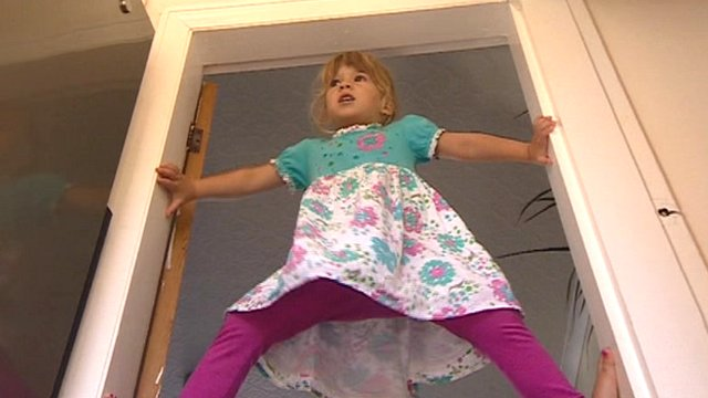 Sofya Dickson, 3, climbing a door frame
