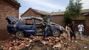 Chinese people walk past a flood damaged vehicle sitting on the bricks at a village in Fangshan district of Beijing, 23 July 2012