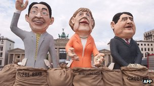 Protesters have placed large effigies of (from L) German Economy Minister Philipp Roesler, German Chancellor Angela Merkel and German Social Democrats (SPD) Chairman Sigmar Gabriel in front of the Brandenberg Gate in Berlin
