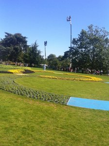 Torchbearer stood inside Olympic rings flower display