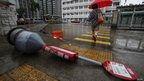 A pedestrian walks past a fallen bus-stop signpost in Hong Kong's northern Tai Po town, 24 July 2012