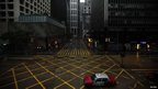 A taxi drives across an empty Des Veous Road in Hong Kong's Central district as Typhoon Vicente approaches, 24 July 2012