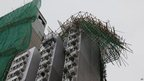 Collapsed scaffolding caused by Typhoon Vicente hangs from a residential building in Hong Kong, 24 July, 2012
