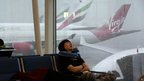 Passengers sleep near planes as heavy rain falls on the airport in Hong Kong, 24 July 2012