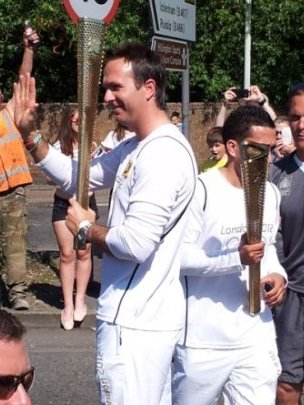 I suspect Michael Vaughan has a friend tweeting on his behalf, hence a very quick photo of him taking the torch