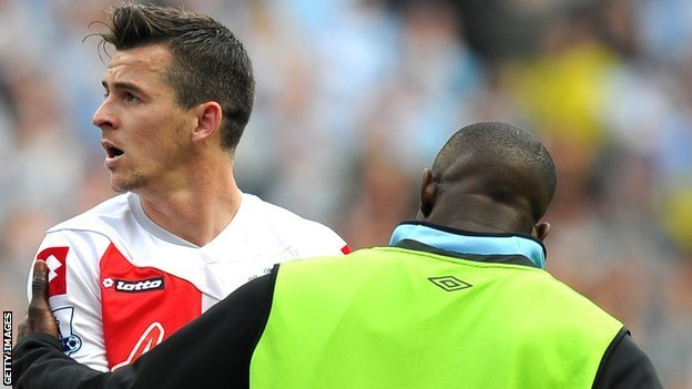 Joey Barton is restrained by a Manchester City substitute