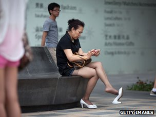 A woman in Beijing looks at a smartphone
