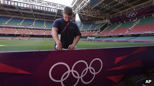 Worker sets up Olympic billboard at the Millennium stadium