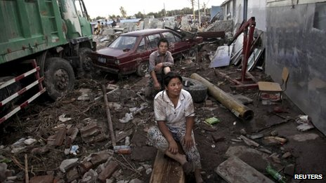 Fangshan residents sit amidst debris and damaged vehicles