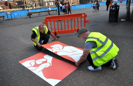 Workmen fix an Olympic pictogram in the Borough of Southwark