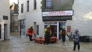 Boat and rescue team in flooded street in Mevagissey