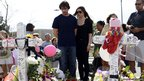 Actor Christian Bale visits the memorial across the street from the Century 16 cinema in Aurora, Colorado.