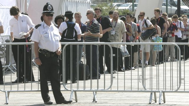 A policeman stands in front of the entrance gate as spectators and members of the media wait to be checked by security at the Millennium Stadium