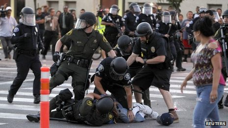 Police arrest a protester in the wake of two fatal police shootings in Anaheim, California 24 July 2012