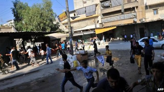 Syrians run for cover as a helicopter flies over Aleppo (24 Jul 2012)