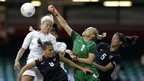 New Zealands goalie Jenny Bindon, centre, punches the ball over Britains Stephanie Houghton, left, during the Group E match.