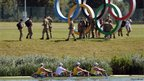 Members of a British army reserve pose for pictures on Olympic rings as an Australian crew row past during practice 