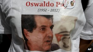 A dissident wears a T-shirt showing a photograph of Cuban activist Oswaldo Paya, centre, and of late dissident leader Laura Pollan, top right, during Paya's burial at a cemetery in Havana