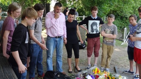 Jay Burgess, Carrie Valentine and teenagers look at floral tributes