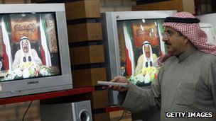 Kuwait man watches emir on TV