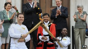 Rhyania Blackett-Codrington passes the Olympic flame to comedian David Walliams