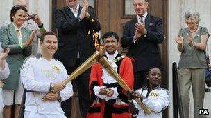 Rhyania Blackett-Codrington passes the Olympic flame to comedian David Walliams