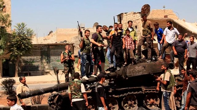 Rebel fighters stand on top of a government tank in Aleppo