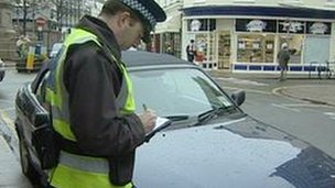 Traffic Warden writing a ticket