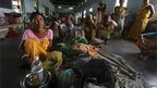 Villagers affected by the ethnic riots sit with their belongings inside a relief camp near Goshaigaon town, in the northeastern Indian state of Assam July 25, 2012