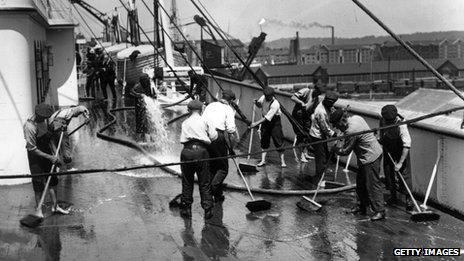 men scrubbing the deck