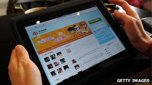 Woman holding tablet showing Sina Weibo