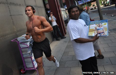 A vendor hands out Olympic scrapbooks as a man runs by