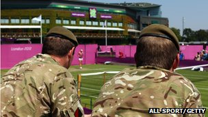Soldiers watch as Maria Sharapova of Russia practices