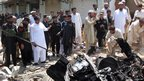 Pakistani security officials inspect the site of a bomb explosion