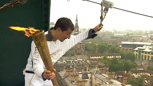 Bear Grylls with the Olympic Torch about to take a zip wire across the Tyne