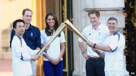 The Duke and Duchess of Cambridge and Prince Harry watch Wai-Ming hand over the London 2012 Olympic Torch to John Hulse during a visit to Buckingham Palace, London