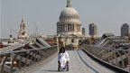 Paralympian Ade Adepitan carried the flame across the Millennium Bridge