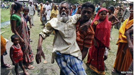 Jahar (C), a 105-year-old villager affected by ethnic riots, is carried by his son to a relief camp near Bijni town in the northeastern Indian state of Assam July 26, 2012