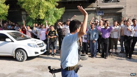 Syrian rebel in northern Aleppo salutes residents chanting anti-government slogans (26 July)