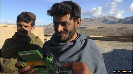 Afghan villagers listen to a radio, given as a gift - Uruzgan 2010