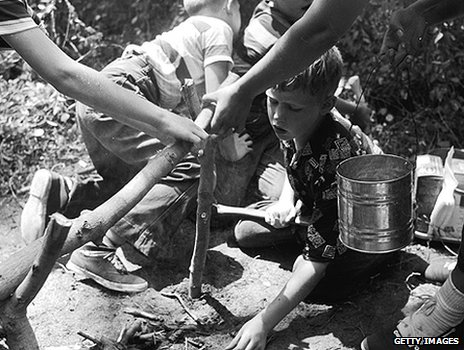 Boys help prepare a camp fire at 1950s summer camp