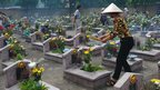 Families visits their late relatives' graves at an official cemetery on the out skirts of Hanoi on the occasion of the National Day for Martyrs and War Invalids on July 27