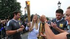 Security staff light the torch for Torchbearer 001 Rosie Hynes at Bushy Park, at the beginning of day 70 of the London 2012 Olympic Torch Relay