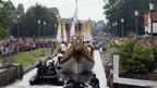 The Queen's rowbarge Gloriana carries the Olympic flame along the river Thames