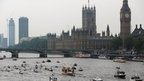 The Queen's royal rowbarge Gloriana carries the Olympic flame along the river Thames past the Houses of Parliament