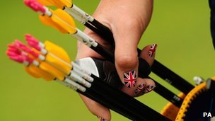 Woman with Union Jack nails selects arrow