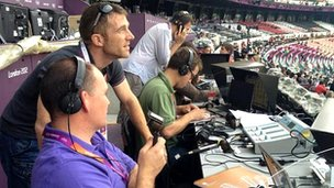 The BBC Radio 5 Live commentary team, including Gordon Farquhar in purple shirt and Mark Pougatch in green, are already hard at work at their desk in the Olympic Stadium