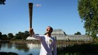 John Harding holds the Olympic flame at Kew Gardens, with the Palm House in the background.